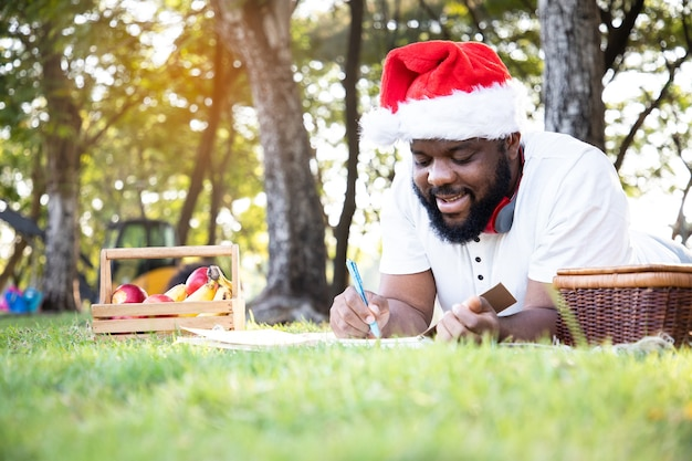 Black african man wearing a santa claus hat and writing a personal diary in the garden