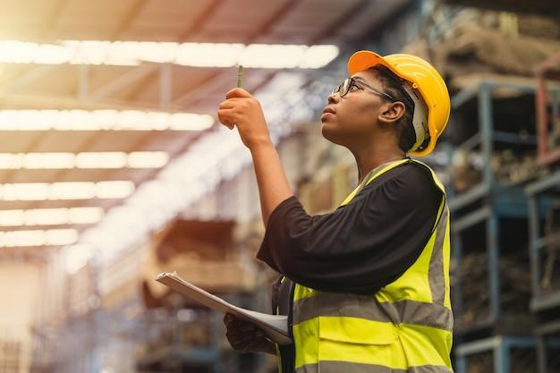 Черные африканские профессиональные женщины-работницы, работающие подсчетом, проверяют инвентарь, производственный контроль запасов в бизнесе, фабрика, промышленность, склад, предупреждают, костюм инженера и шлем для безопасности