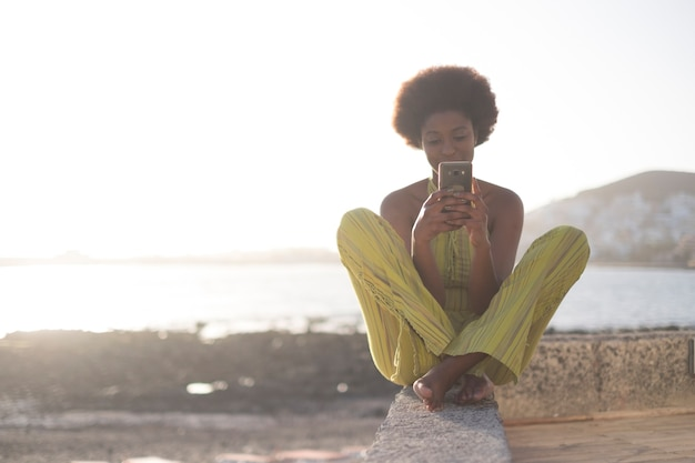 Black african race young beautiful model girl 25 years old use the phone and check internet social media sitting on a wall near the ocean and water with bright sunset . happy leisure people