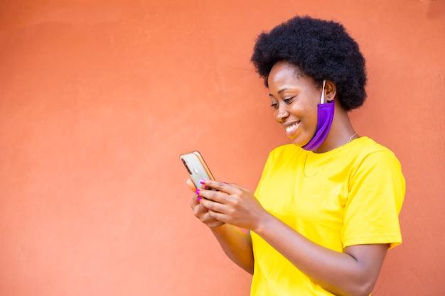 彼女の携帯電話から良いニュースを受け取った後興奮している黒人のアフリカの女性