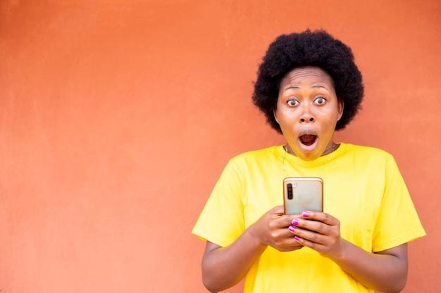Черная африканская женщина чувствует себя взволнованной после получения хороших новостей со своего мобильного телефона