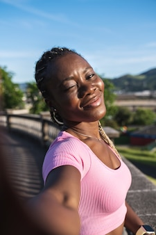 Black african woman taking a selfie holding the phone with her hands very happy and giving a kiss in a public park on a very sunny day and gray sky. black woman in causal lifestyle clothing