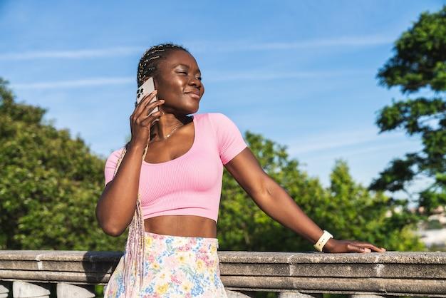 非常に晴れた日と灰色の空の公共の公園で非常に幸せに携帯電話で話している黒人のアフリカの女性。因果的なライフスタイルの服を着た黒人女性