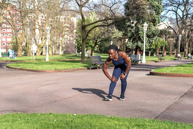 Black african woman warming up and doing knee stretches to start doing sports in a public street park on a sunny day