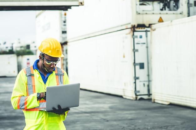 Черный африканский рабочий, работающий в сфере логистики, использует ноутбук для контроля погрузки контейнеров в портовых грузах для бригадира по импортным и экспортным товарам, который смотрит в будущее