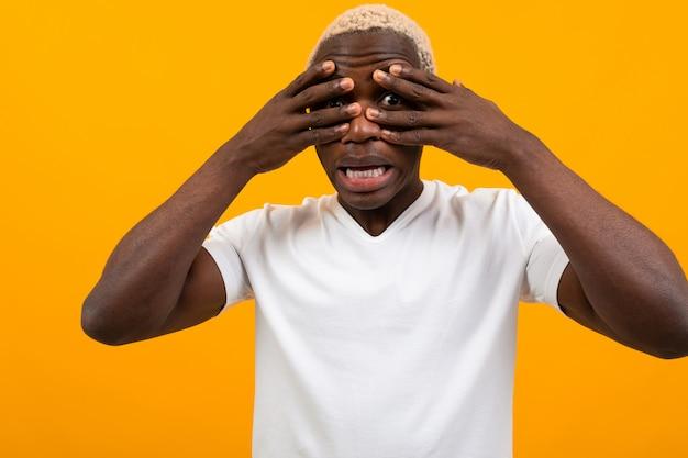 黒のアフリカの若い男が黄色の手で彼の顔を短所