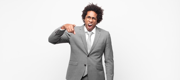 怒り狂った上司のように見える怒りの攻撃的な表情で正面を向いている黒人のアフロビジネスマン
