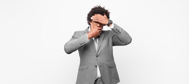 Черный афро-бизнесмен, закрывающий лицо обеими руками, говорит