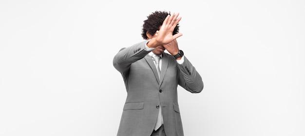 Черный афро бизнесмен, прикрыв лицо рукой и подняв другую руку вперед, чтобы остановиться