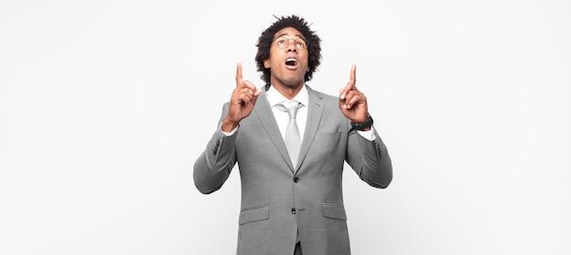 Черный афро-бизнесмен чувствует благоговение и с открытым ртом, указывая вверх с шокированным и удивленным взглядом