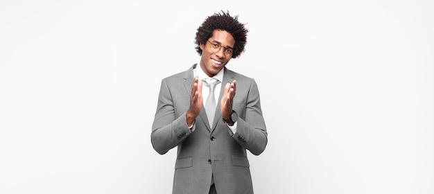 黒人のアフロビジネスマンが幸せで成功したと感じ、笑顔で手をたたき、拍手でおめでとうと言います
