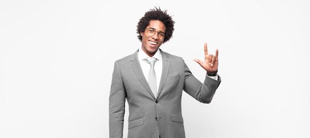 黒人のアフロビジネスマンが幸せで、楽しく、自信を持って、前向きで反抗的で、手でロックやヘビーメタルのサインを作る