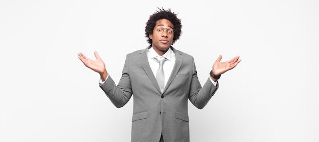 黒人のアフロビジネスマンが困惑して混乱していると感じ、疑ったり、重みを付けたり、面白い表現でさまざまなオプションを選択したりする