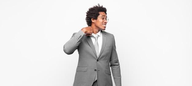 Черный афро-бизнесмен чувствует стресс, тревогу, усталость и разочарование, дергает за шею рубашки, выглядит разочарованным из-за проблемы