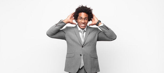 Black afro businessmanfeeling stressed, worried, anxious or scared, with hands on head, panicking at mistake