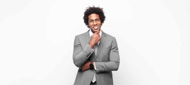 黒人のアフロビジネスマンが幸せそうに見えて、あごに手を当てて笑って、疑問に思ったり質問したり、オプションを比較したりする