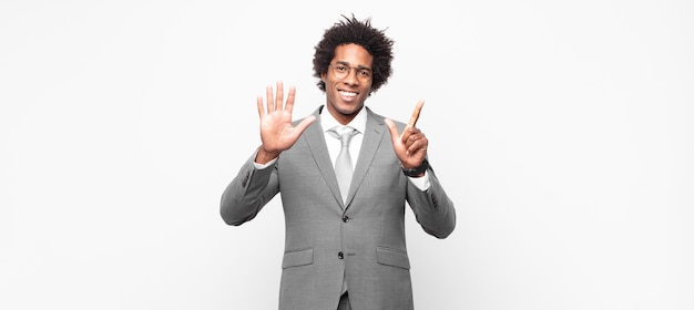 Black afro businessmansmiling and looking friendly, showing number seven or seventh with hand forward, counting down