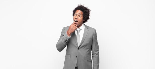 Черный афро-бизнесмен с удивленным, нервным, встревоженным или испуганным взглядом смотрит в сторону в сторону места для копирования