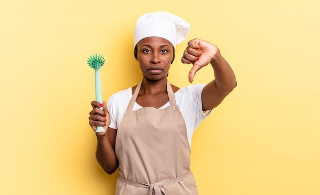 黒人のアフロシェフの女性は、真剣な表情で親指を下に向けて、十字架、怒り、イライラ、失望、または不満を感じています。食器洗いのコンセプト