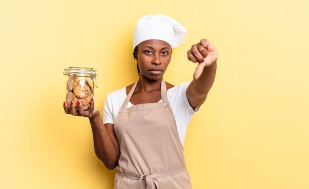 黒人のアフロシェフの女性は、真剣な表情で親指を下に向けて、十字架、怒り、イライラ、失望、または不満を感じています。クッキーの概念