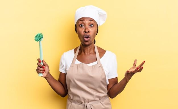 Черная афро-шеф-повар чувствует себя чрезвычайно шокированной и удивленной, встревоженной и панической, с напряженным и испуганным взглядом. концепция очистки посуды