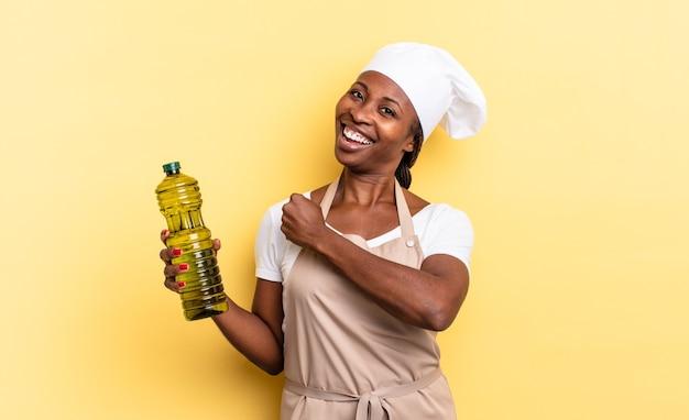 黒人のアフロシェフの女性は、挑戦に直面したり、良い結果を祝ったりするときに、幸せで、前向きで、成功し、やる気を感じています。オリーブオイルの概念