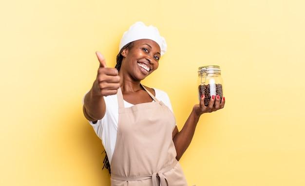 黒人のアフロシェフの女性は、誇り高く、のんきで、自信を持って幸せに感じ、親指を立てて前向きに笑っています。コーヒー豆の概念