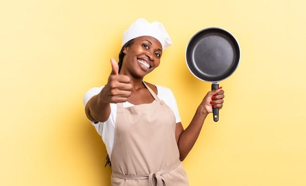 黒人のアフロシェフの女性は、誇り高く、のんきで、自信を持って幸せに感じ、親指を立てて前向きに笑っています