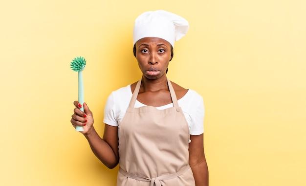 黒人のアフロシェフの女性は、不幸な表情で悲しみと泣き言を感じ、否定的で欲求不満の態度で泣いています。食器洗いのコンセプト