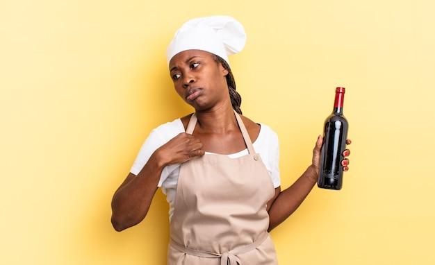 Черная афро-шеф-повар чувствует стресс, тревогу, усталость и разочарование, тянет рубашку за шею и выглядит разочарованной из-за проблемы. концепция бутылки вина