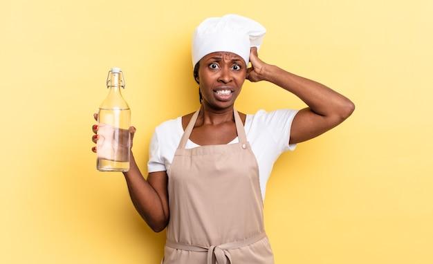 흑인 아프로 셰프 여성은 머리에 손을 얹고 물병을 들고 실수로 당황하고, 스트레스를 받고, 걱정하고, 불안하거나 겁을 먹고 있습니다.