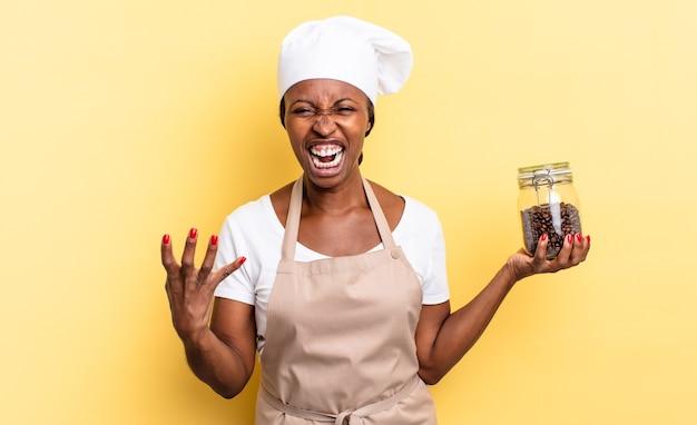 흑인 아프로 셰프 여성이 화가 나고 짜증이 나며 비명을 지르거나 당신에게 무슨 문제가 있는 것처럼 보입니다. 커피 콩 개념