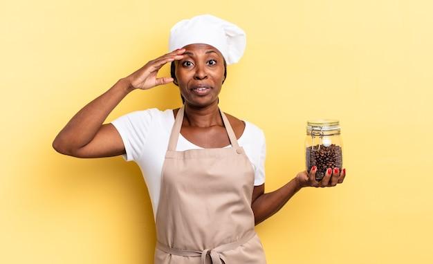 Черная афро-шеф-повар выглядит счастливой, удивленной и удивленной, улыбается и понимает удивительные и невероятные хорошие новости. кофе в зернах концепция