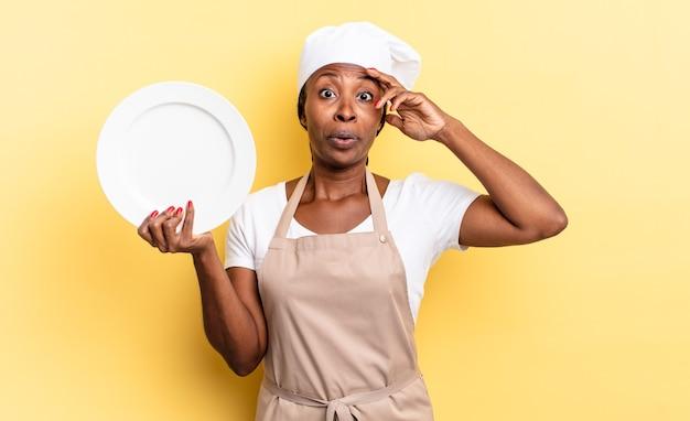 Черная афро-шеф-повар выглядит счастливой, удивленной и удивленной, улыбается и понимает удивительные и невероятные хорошие новости. концепция пустой тарелки