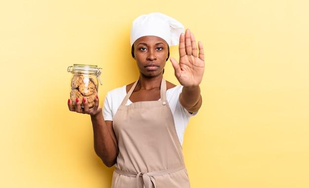 Черная афро-шеф-повар женщина выглядит серьезной, суровой, недовольной и сердитой, показывая открытую ладонь, делая жест остановки. концепция куки