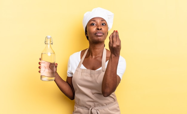 Black afro chef woman making capice or money gesture, telling you to pay your debts! holding a water bottle
