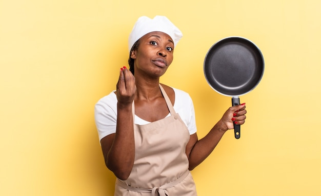 Black afro chef woman making capice or money gesture, telling you to pay your debts!