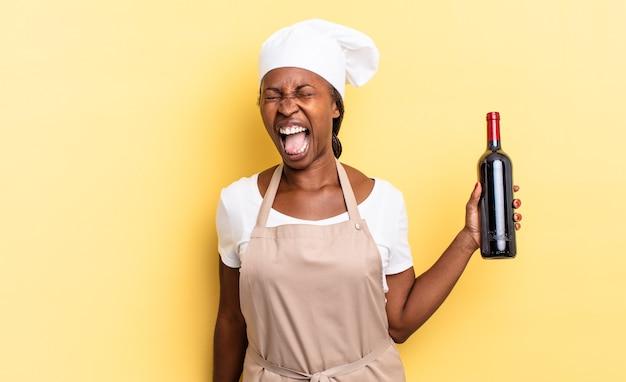 흑인 아프로 셰프 여성은 매우 화나고, 좌절하고, 화를 내거나 짜증을 내며 공격적으로 소리를 지르며 아니오를 외쳤습니다. 와인 병 개념