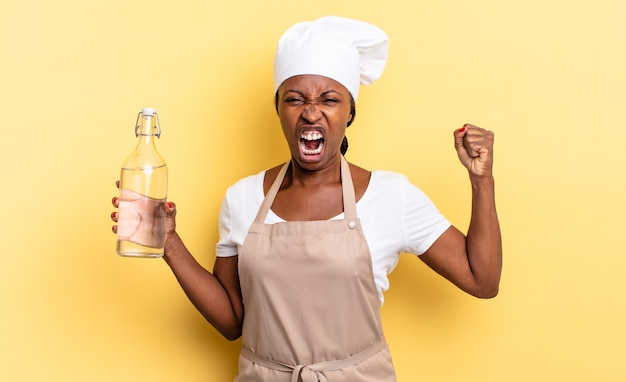 흑인 아프로 셰프 여성은 화난 표정으로 공격적으로 외치거나 물병을 들고 성공을 축하하는 주먹을 꽉 쥐었다