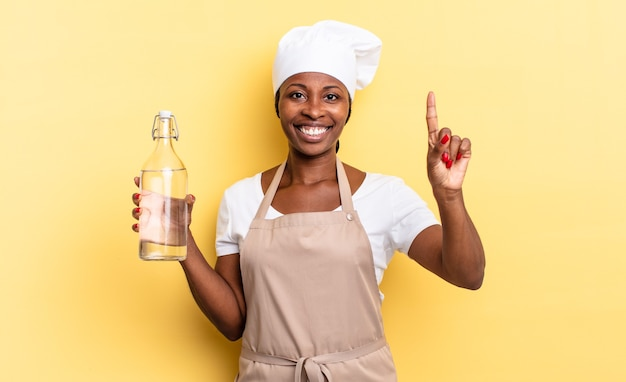 흑인 아프로 셰프 여성은 웃고 친근하게 보이며 손으로 1위 또는 1위를 보여주며 물병을 들고 카운트다운