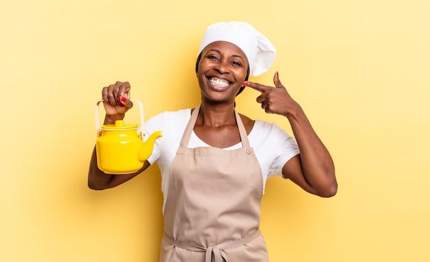 Черная афро-шеф-повар уверенно улыбается, указывая на собственную широкую улыбку, позитивное, расслабленное, удовлетворенное отношение. концепция чайника