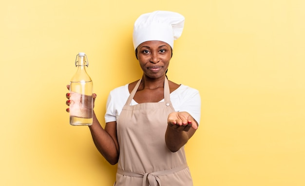 흑인 아프로 셰프 여성은 친절하고 자신감 있고 긍정적인 표정으로 행복하게 웃고 있으며 물병을 들고 있는 물건이나 개념을 제공하고 보여줍니다.