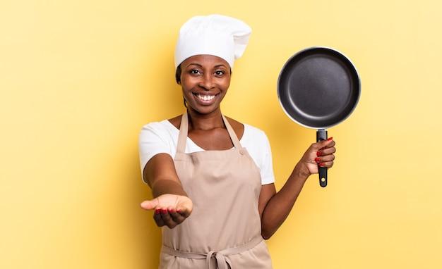 Черная афро-шеф-повар счастливо улыбается с дружелюбным, уверенным, позитивным взглядом, предлагая и показывая объект или концепцию