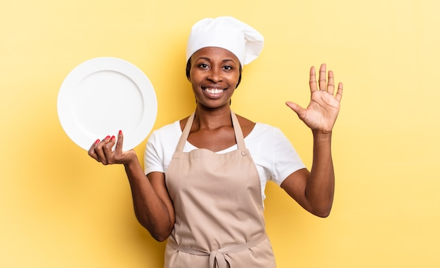 Black afro chef woman smiling and looking friendly, showing number five or fifth with hand forward, counting down. empty plate concept