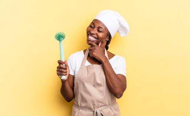 흑인 아프로 셰프 여성은 턱에 손을 대고 행복하고 자신감 있는 표정으로 웃으면서 궁금해하고 옆을 바라보고 있습니다. 청소 접시 개념
