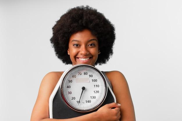 バランスまたはスケールを持つ黒のアフロフィットネス女性