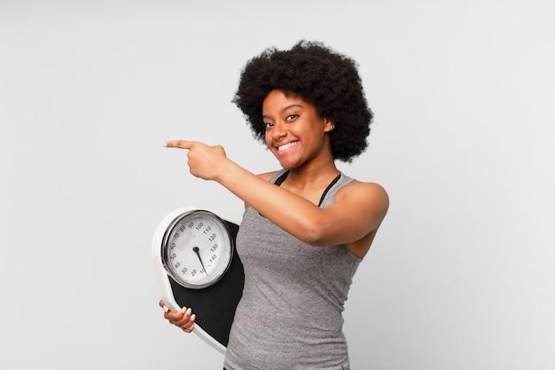 Черная афро фитнес женщина с балансом или весами