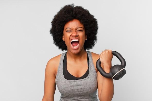 Черная афро фитнес женщина с гантелями