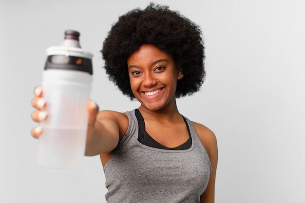 Черная афро-фитнес-женщина с полотенцем и водой