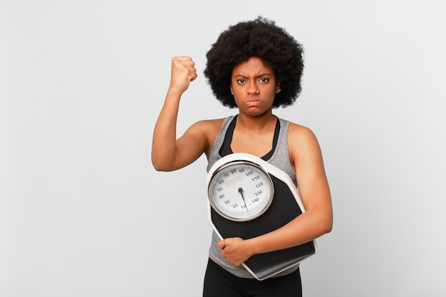 Black afro fitness woman with a balance or scale